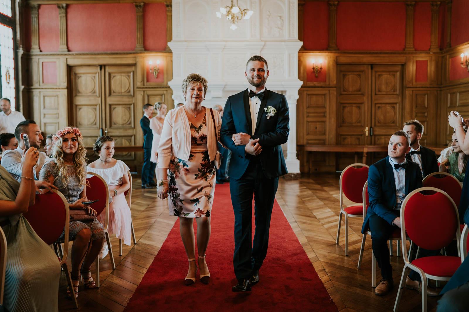 Le marié arrive à la mairie au bras de sa maman.