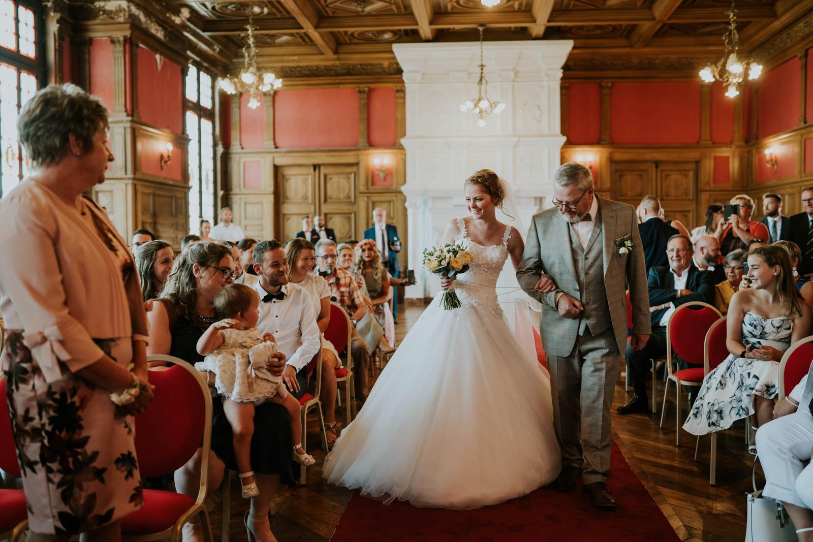 La mariée arrive à la mairie au bras de son papa.